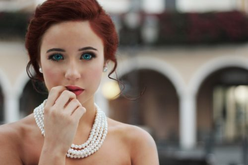 red hair woman pearls