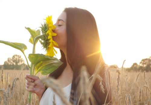woman smelling a sunflower