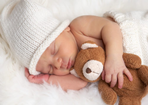 newborn wearing a beanie with a teddy